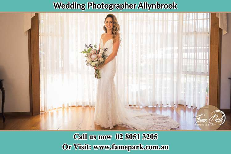The Bride in the window holding bouquet of flowers Allynbrook