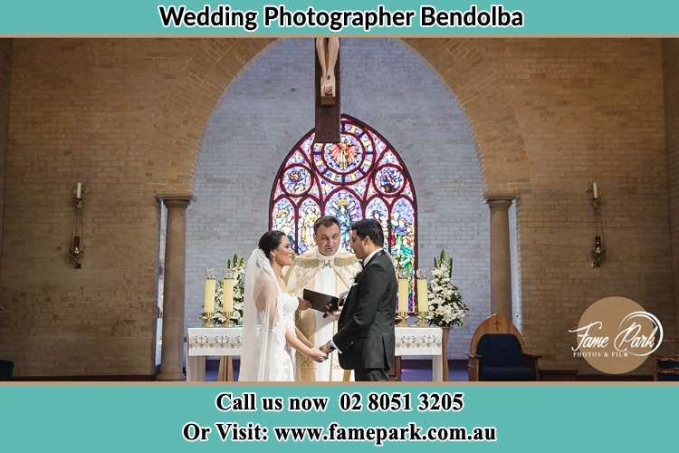 Photo of the Bride and the Groom with the Priest at the altar Bendolba NSW 2420