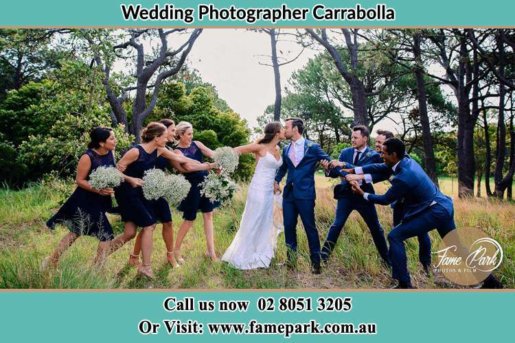 Photo of the Bride and the Groom kissing while teasing by their entourage Carrabolla NSW 2311