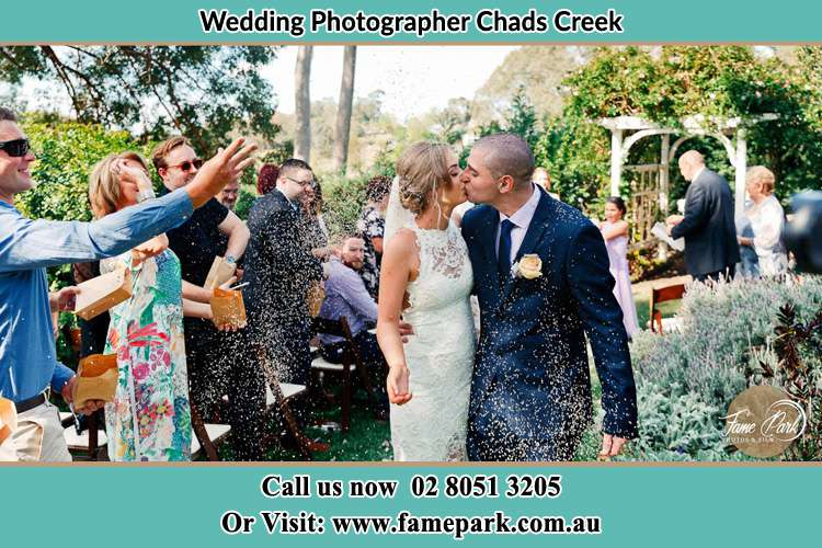 Photo of the Bride and the Groom kissing while showering rice by their visitors Chads Creek NSW 2311