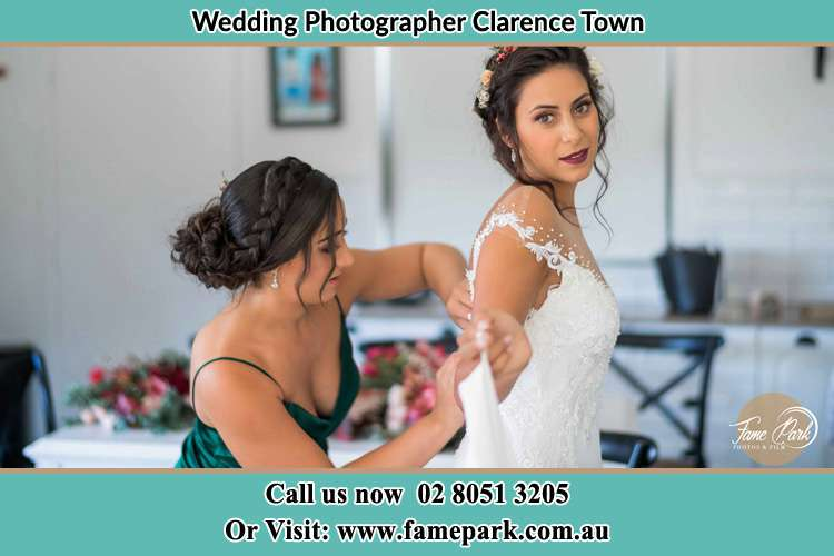 Photo of the Brides getting help from her bridesmaid to fit her wedding gown Clarence Town NSW 2321