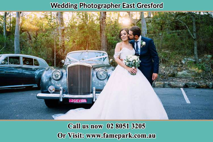Photo of the Groom kissing the Bride in front of the bridal car East Gresford NSW 2311