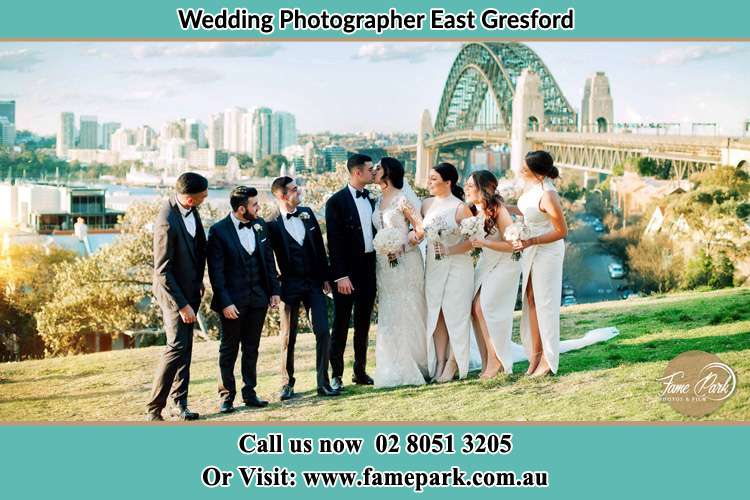 Photo of the Groom and the Bride kissing with their entourage near the bridge East Gresford NSW 2311