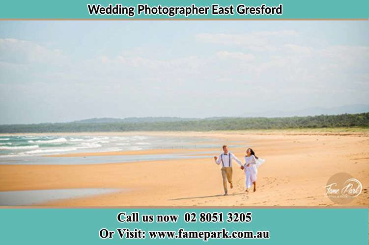 Bride and Groom running on the beach East Gresford