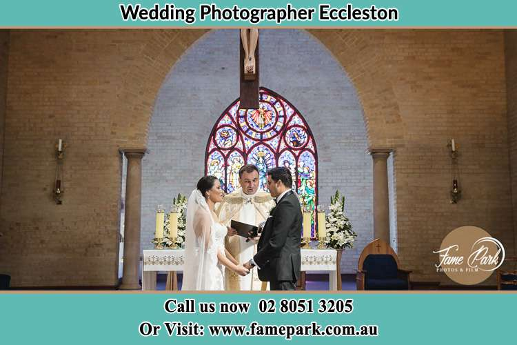 Photo of the Bride and the Groom with the Priest at the altar during wedding ceremony Eccleston NSW 2311