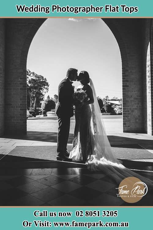 Photo of the Groom and the Bride kissing at the front of the church Flat Tops NSW 2420