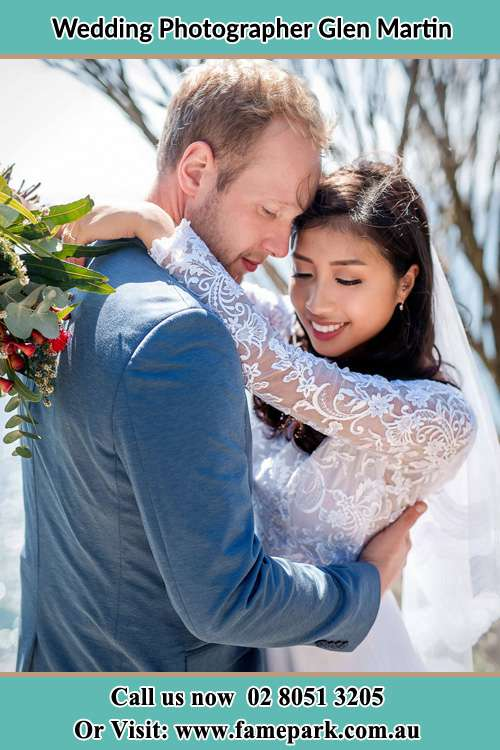 Bride and Groom Holds each other while holding a bouquet of floweers Glen Martin