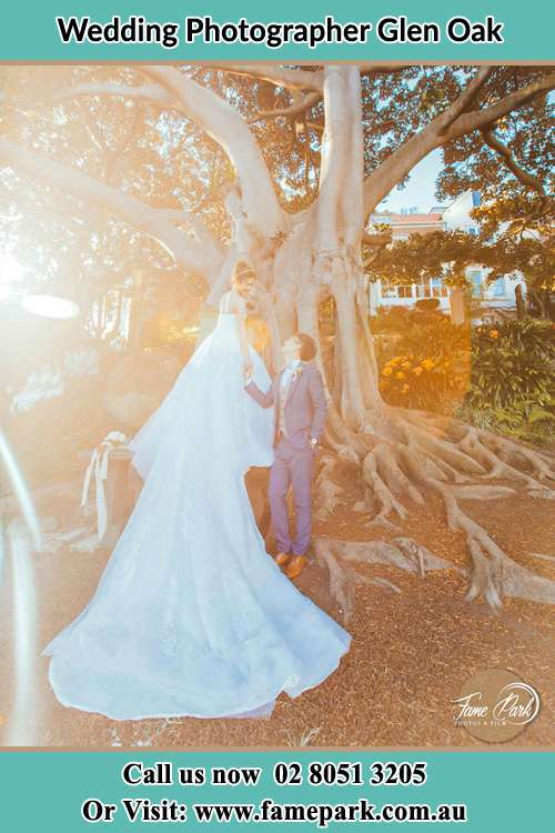 Photo of the Bride and the Groom looking each other beside the tree Glen Oak NSW 2320