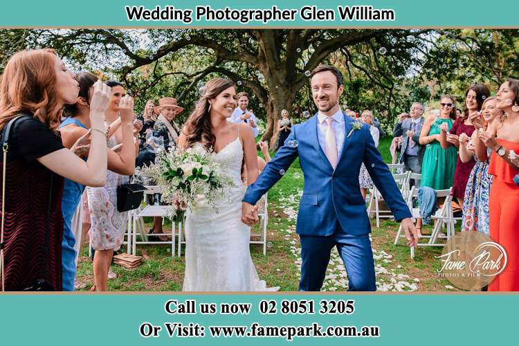 Photo of the Bride and the Groom holding hands while showering bubbles by their visitors Glen William NSW 2321