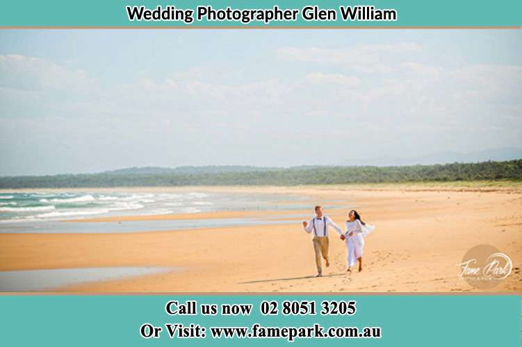 Bride and Groom running at the beach Glen William