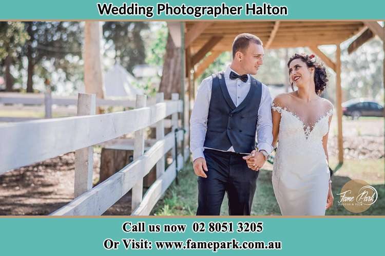 Photo of the Groom and the Bride looking each and holding hands while walking Halton NSW 2311