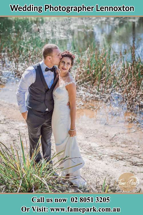 Photo of the groom kissing his Bride near the lake Lennoxton NSW 2421