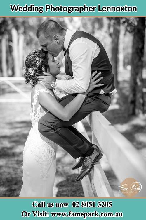 Photo of the Groom sitting on the fence kissing his Bride to the forehead Lennoxton NSW 2421