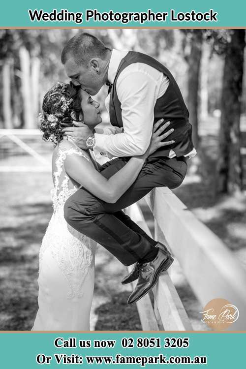 Photo of the Groom sitting on the fence kissing his Bride at the forehead Lostock NSW 2311
