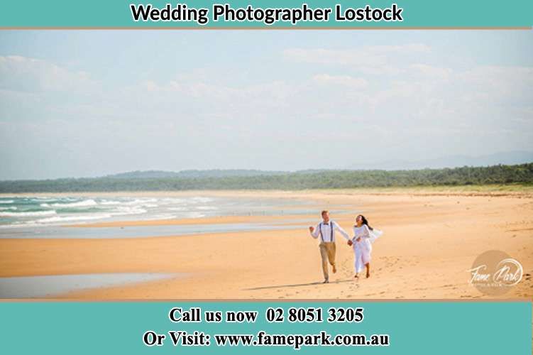 Photo of the Groom and the Bride walking at the sea shore Lostock NSW 2311
