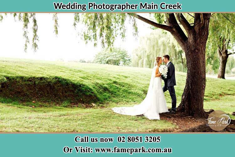 Photo of the Bride and the Groom kissing under the tree Main Creek NSW 2420