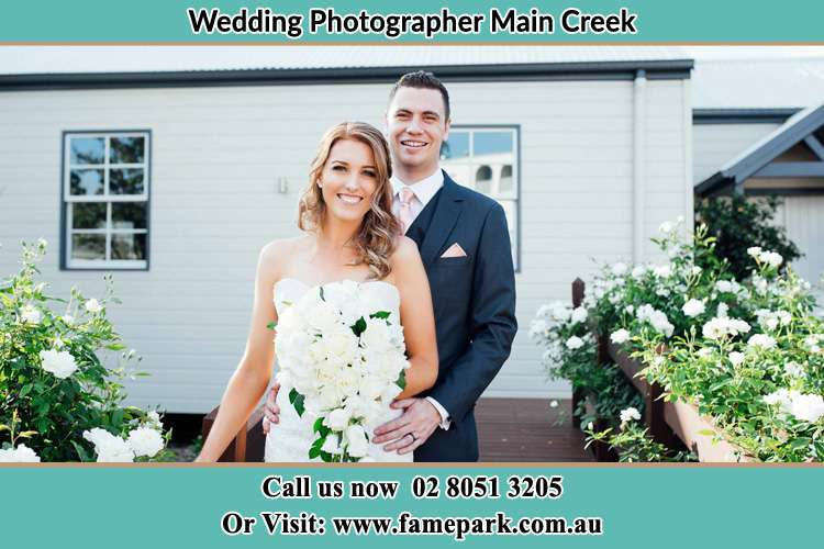 The Bride and the Groom smiling on camera at the front of the house Main Creek NSW 2420