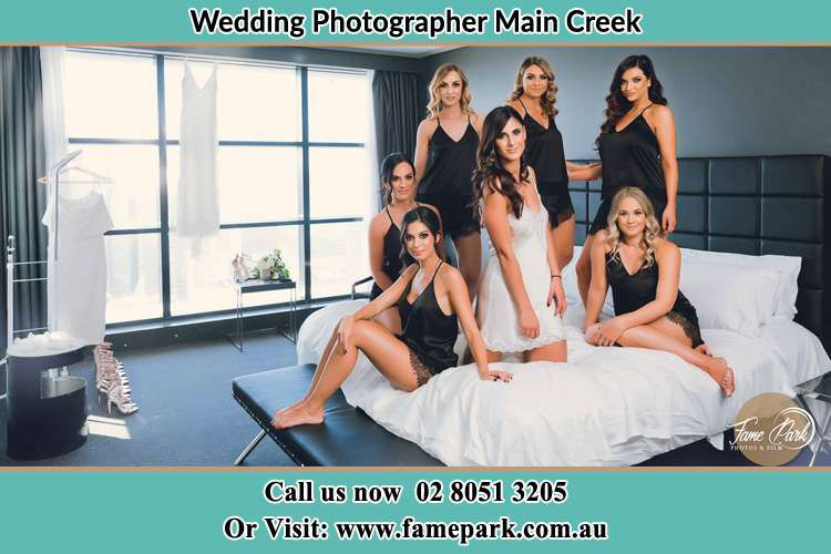 Photo of the Bride and the bridesmaids wearing lingerie on the bed Main Creek NSW 2420