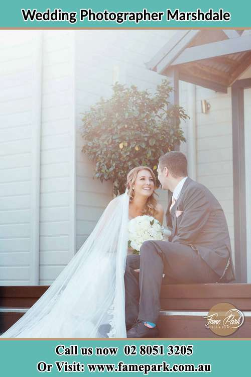 Photo of the Bride and the Groom looking each other while sitting on the staircase Marshdale NSW 2420