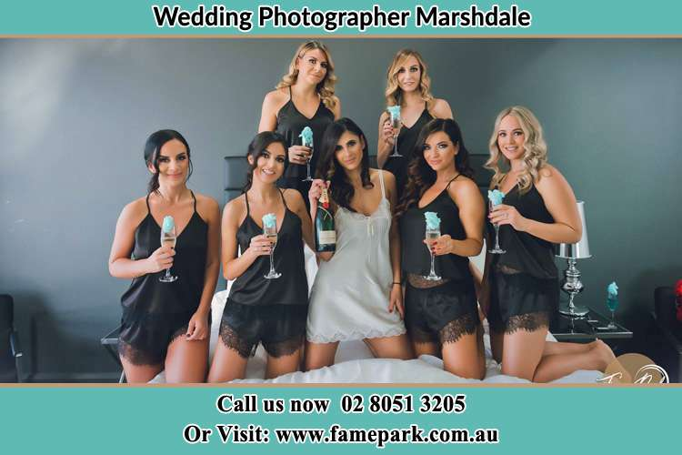 Photo of the Bride with the bridesmaids wearing lingerie while holding glass of wine on bed Marshdale NSW 2420