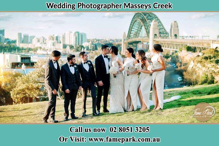 Photo of the Groom and the Bride kissing together with the entourage near the bridge Masseys Creek NSW 2331