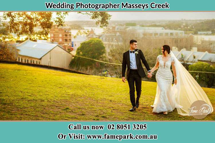 Photo of the Groom and the Bride holding hands while walking at the yard Masseys Creek NSW 2331