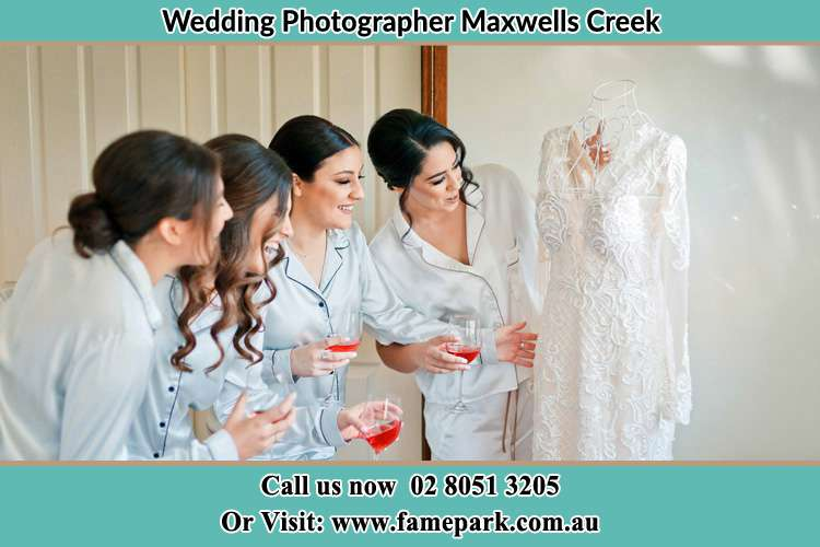 Photo of the Bride with the bridesmaids looking at her wedding gown Maxwells Creek NSW 2420