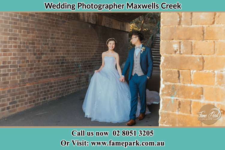Photo of the Bride and the Groom holding hands while walking Maxwells Creek NSW 2420