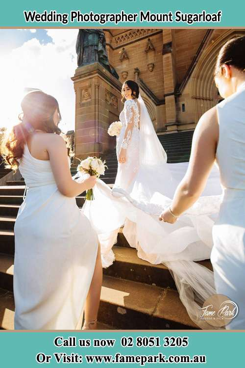 Photo of the Bride smiling at her bridesmaid holding the tail of her wedding gown at the front of the church Mount Sugarloaf NSW 2286