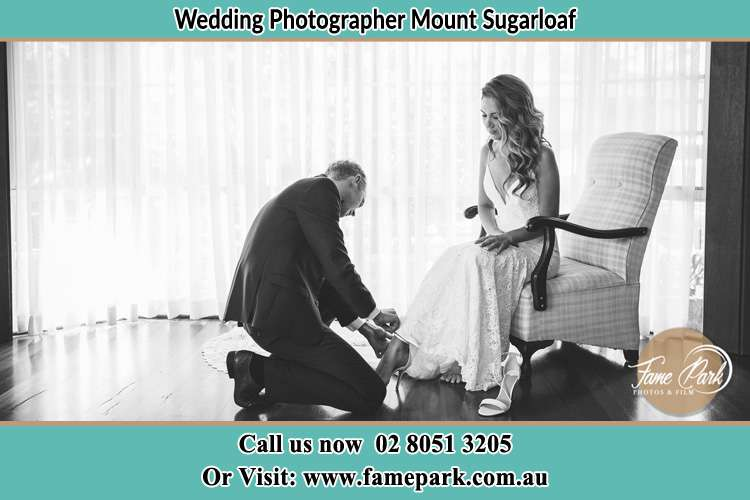 Groom putting shoes to the Bride Mount Sugarloaf