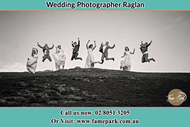 Photo of the Bride and the Groom with the entourage having a jump shot Raglan NSW 2795