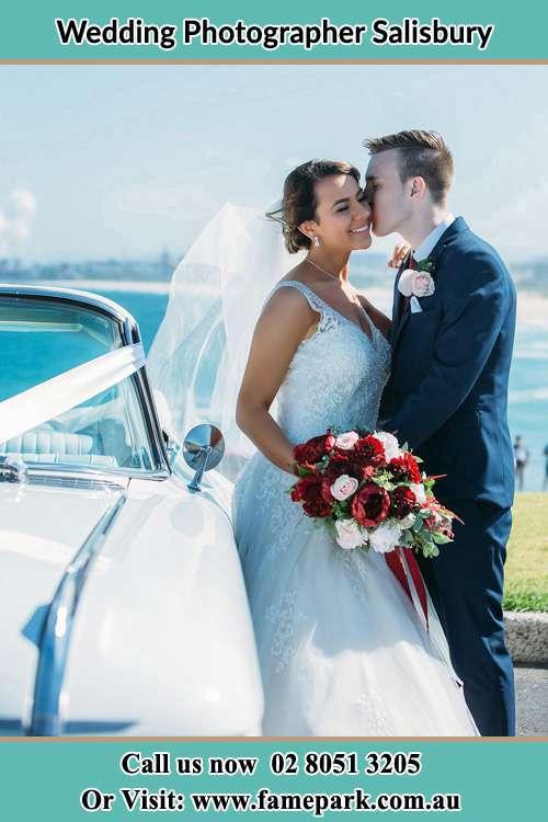 Groom kiss the Bride beside their bridal car near the shore Salisbury