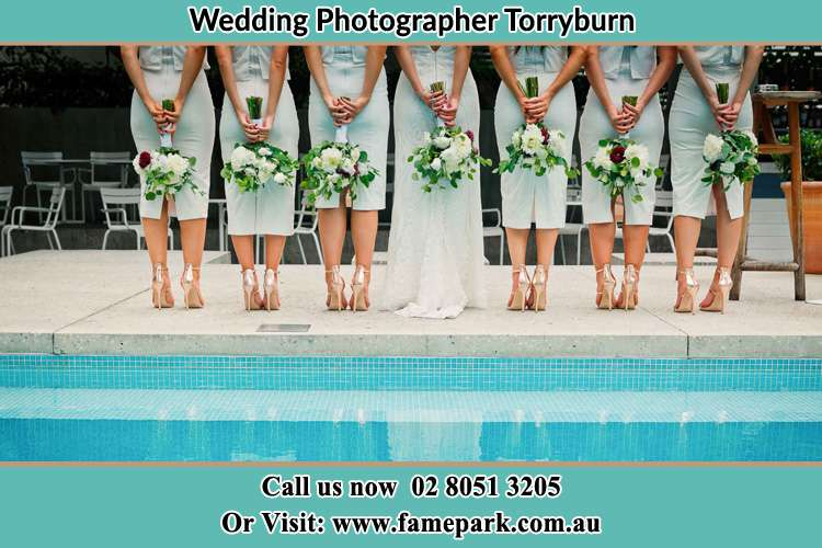 Behind photo of the Bride and her bridesmaids holding flower besides the pool Torryburn NSW 2358