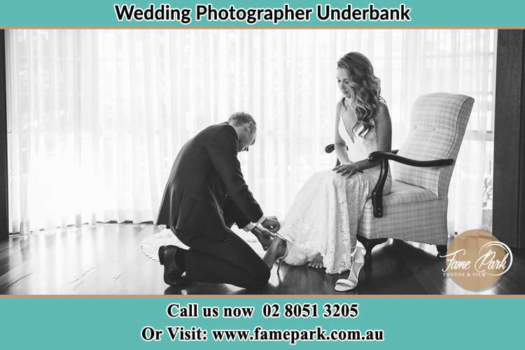 Groom putting shoes to the Bride Underbank