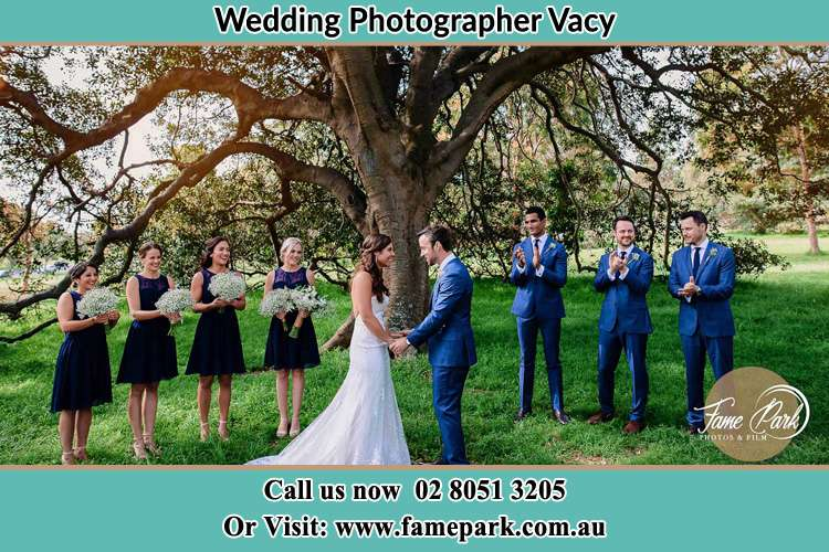 Bride and Groom under the tree with thier secondary sponsor Vacy
