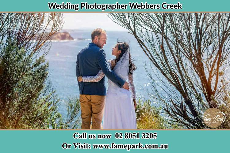 Photo of the Groom and the Bride happily looking each other at the sea front Wangat NSW 2420