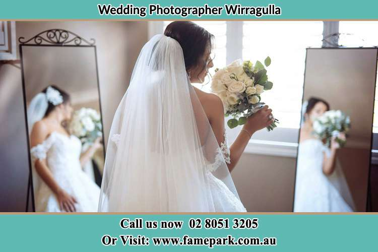 The Bride looking at the mirror while holding a bouquet of flowers Wirragulla